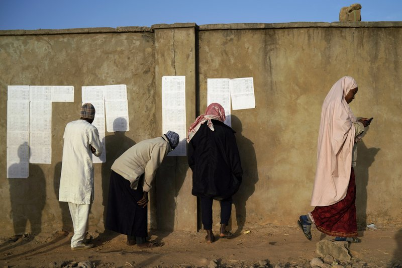 Nigerians check voters' lists at a polling station in Kaduna, Nigeria, Saturday, Feb. 16, 2019. Nigeria's electoral commission delayed the presidential election until Feb. (AP Photo/Jerome Delay)