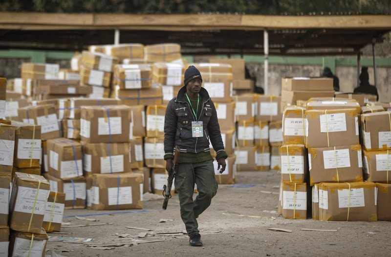 A police officer keeps guard over electoral materials still stacked in boxes at the offices of the Independent National Electoral Commission in Kano, in northern Nigeria Saturday, Feb. (AP Photo/Ben Curtis)