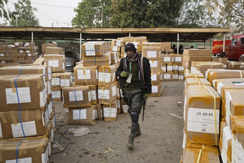 A police officer keeps guard over electoral materials still stacked in boxes at the offices of the Independent National Electoral Commission in Kano, in northern Nigeria, Saturday, Feb. (AP Photo/Ben Curtis)