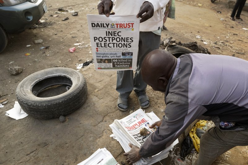 Newspaper sellers bring copies of a newspaper which managed to print the news of the postponement in time, in the morning at a newspaper stand in Kano, in northern Nigeria, Saturday, Feb. (AP Photo/Ben Curtis)
