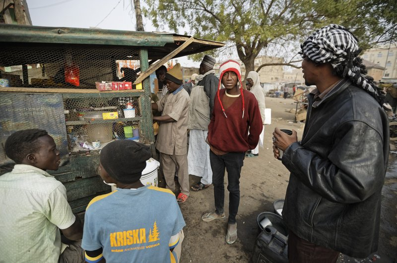Newspaper distributors take hot drinks from a roadside stall in the morning next to a newspaper stand in Kano, in northern Nigeria Saturday, Feb. (AP Photo/Ben Curtis)