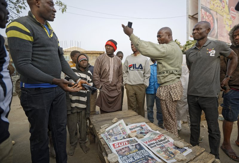 Nigerians discuss the overnight developments at a newspaper stand selling copies of papers that printed before the postponement was announced, in the morning in Kano, in northern Nigeria Saturday, Feb. (AP Photo/Ben Curtis)