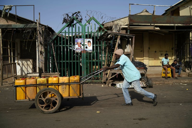 A Nigerian man pushs his wheelbarrow by the closed central market in Kaduna, Nigeria, Saturday, Feb. 16, 2019. (AP Photo/Jerome Delay)