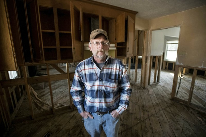 Kevin Tovornik poses for a photo in the kitchen of his home damaged by flooding from Hurricane Florence near the Crabtree Swamp Friday, Feb. (AP Photo/Sean Rayford)