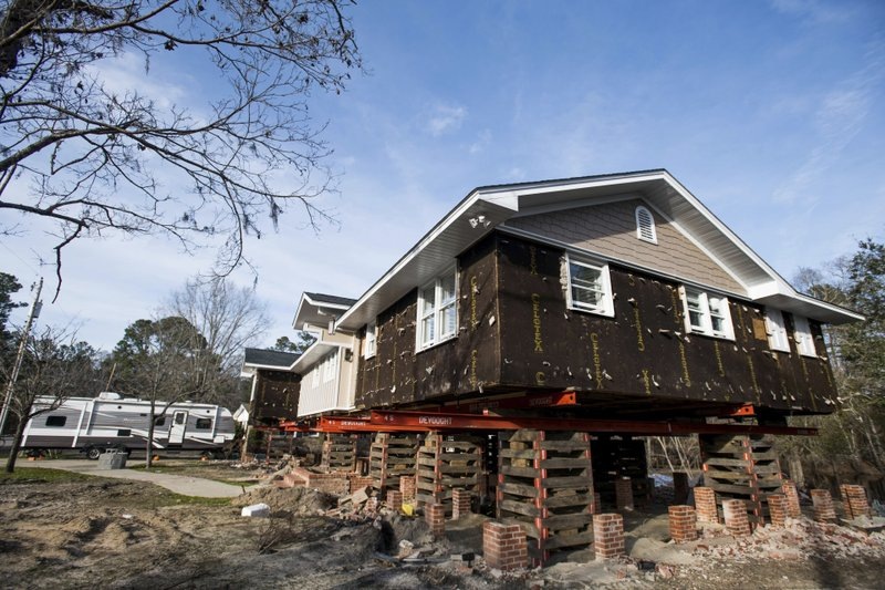 A travel camper sits in the driveway outside of a home in the process of being raised after being damaged by floodwaters from Hurricane Florence Friday, Feb. (AP Photo/Sean Rayford)