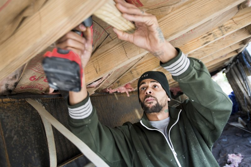 Joshua Voaklander works to repair his home damaged by flooding from Hurricane Florence Friday, Feb. 1, 2019, in Conway, S. (AP Photo/Sean Rayford)