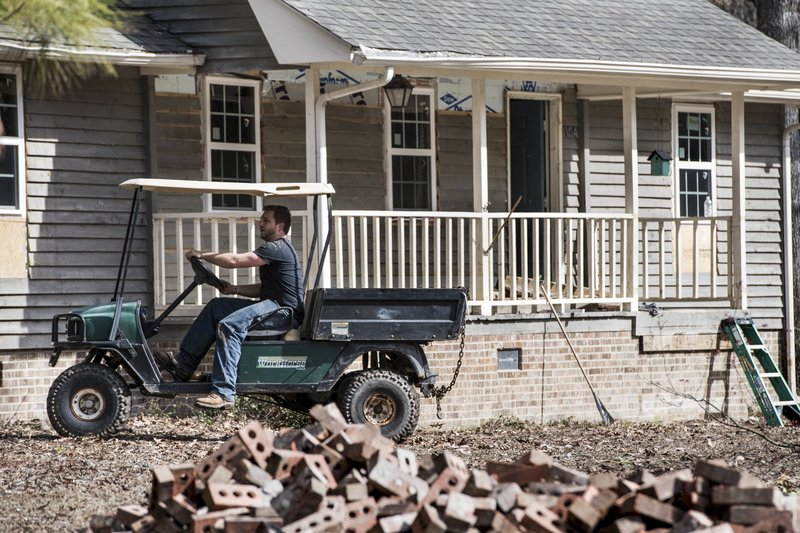 Austin Black works to repair a home damaged by flooding from Hurricane Florence near the Crabtree Swamp Friday, Feb. (AP Photo/Sean Rayford)