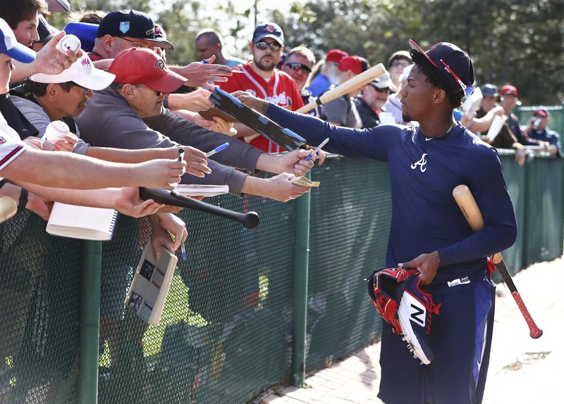 Fans work the fence line as Atlanta Braves outfielder Ronald Acuna Jr. pauses to sign some autographs as he leaves the batting cages after working out at spring training baseball, Saturday, Feb. (Curtis Compton/Atlanta Journal-Constitution via AP)
