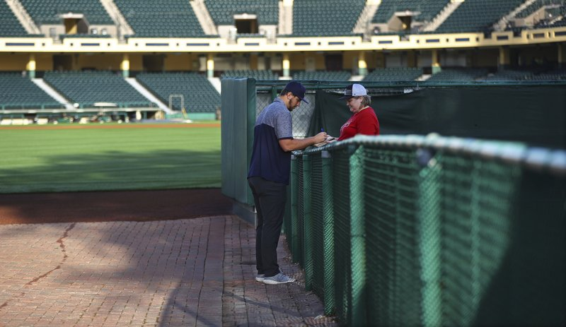 Atlanta Braves pitcher Patrick Weigel signs an autograph for Jeanette Marlier at the gate at baseball spring training in Kissimmee, Fla. (Curtis Compton/Atlanta Journal-Constitution via AP)