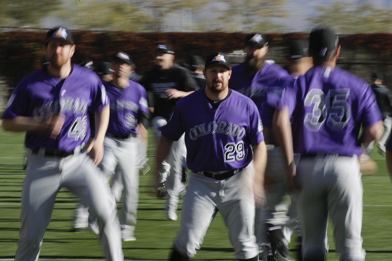 Colorado Rockies relief pitcher Bryan Shaw warms up at their spring baseball training facility in Scottsdale, Ariz. (AP Photo/Chris Carlson)