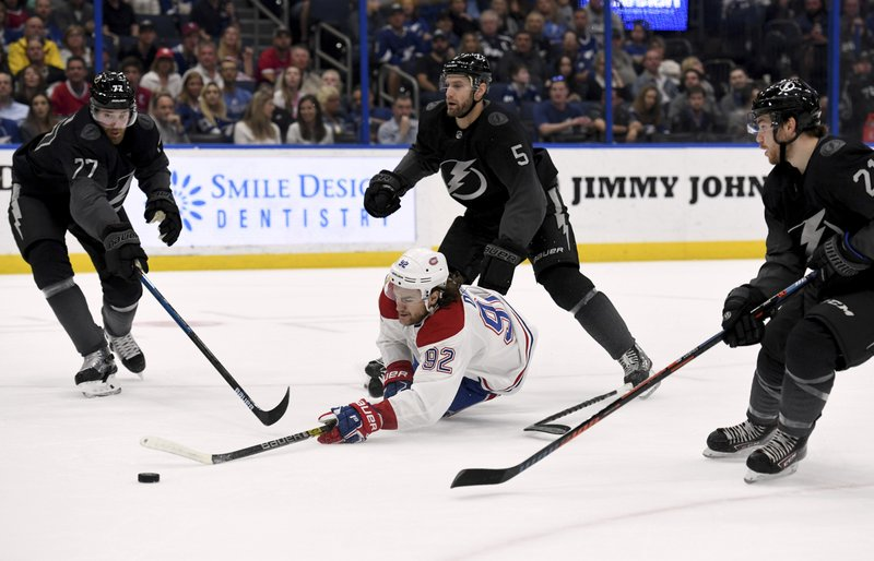 Montreal Canadiens left wing Jonathan Drouin (92) shoots after being tripped by Tampa Bay Lightning defenseman Dan Girardi (5) during the first period of an NHL hockey game Saturday, Feb. (AP Photo/Jason Behnken)