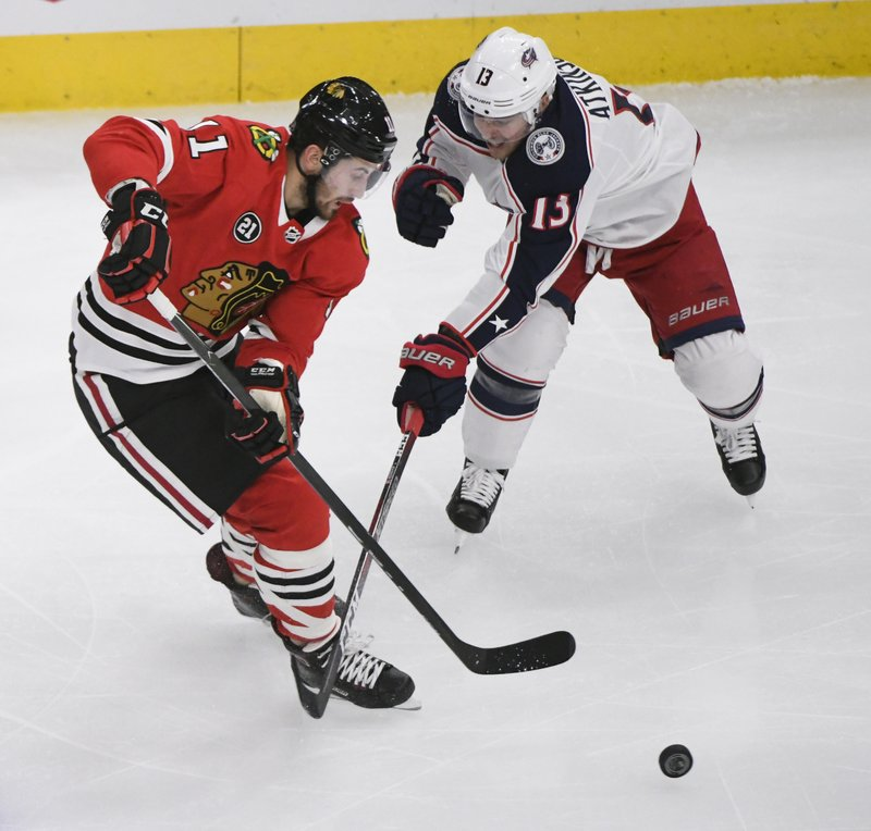Chicago Blackhawks left wing Brendan Perlini (11) and Columbus Blue Jackets right wing Cam Atkinson (13) fight for the puck during the second period of an NHL hockey game Saturday, Feb. (AP Photo/Matt Marton)