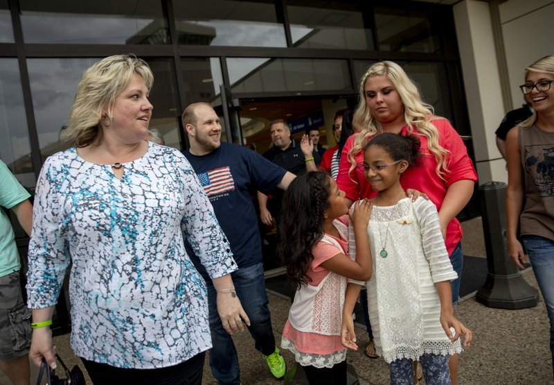 FILE - In this May 28, 2018, file photo, Laurie Holt, left, walks out of the airport with her son, Josh Holt, walking behind her, after returning to Salt Lake City after Josh and his family received medical care and visited President Donald Trump in Washington. (AP Photo/Kim Raff, File)