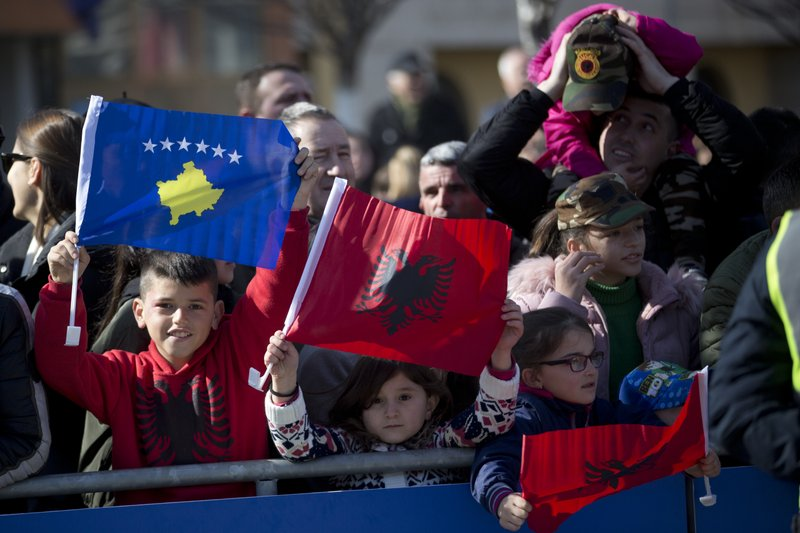Kosovars waving national flags pose for a photo, during celebrations to mark the 11th anniversary of independence, in Pristina, Sunday, Feb. (AP Photo/Visar Kryeziu)(AP Photo/Visar Kryeziu)