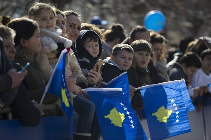 Kosovars wave national flags as they wait to watch a military parade, during celebrations to mark the 11th anniversary of independence in Pristina, Sunday, Feb. (AP Photo/Visar Kryeziu)