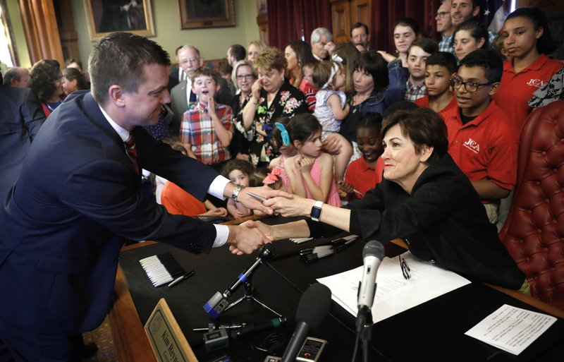 FILE - In this May, 4, 2018, file photo, Iowa Gov. Kim Reynolds, right, greets Iowa Senate Majority Leader Jack Whitver, left, after a bill signing ceremony in her formal office at the Statehouse in Des Moines, Iowa. (AP Photo/Charlie Neibergall, File)