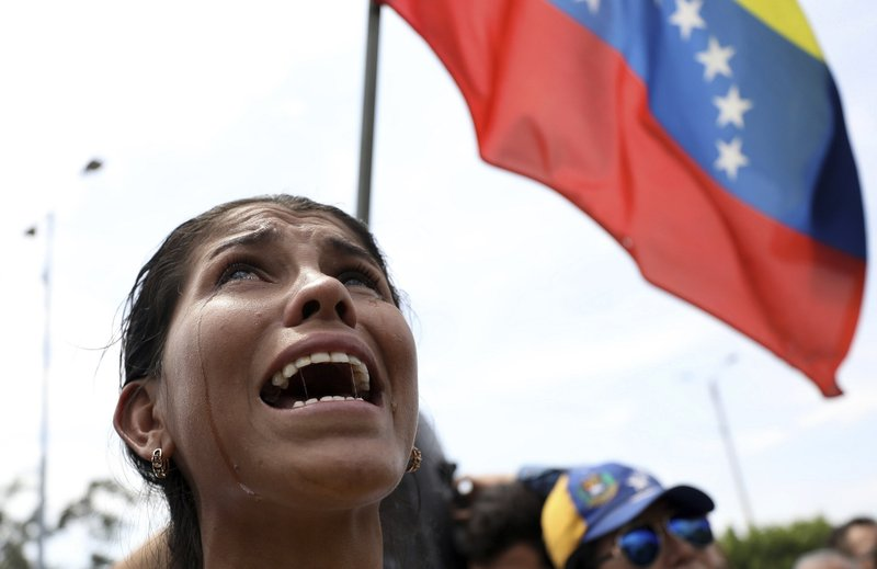 Venezuelan migrant Yanela Aleman cries as she sings her national anthem in La Parada, near Cucuta, Colombia, on the border with Venezuela, Sunday, Feb. (AP Photo/Fernando Vergara)