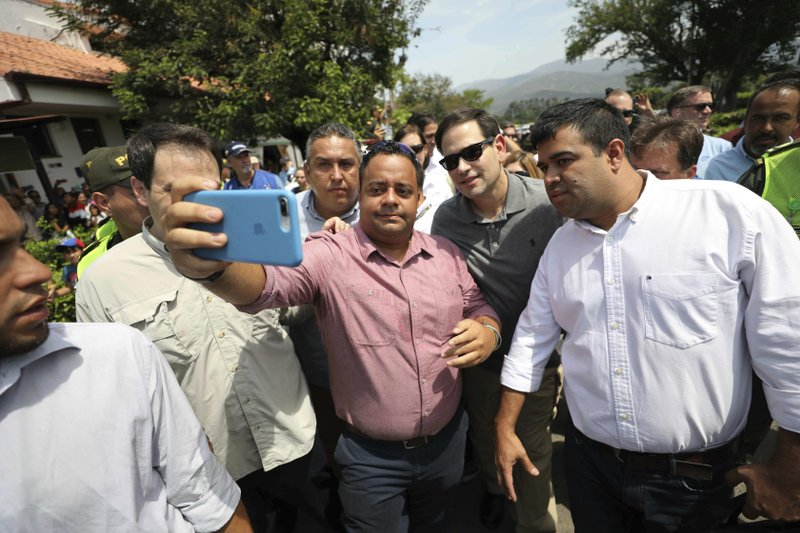 U.S. Senator Marco Rubio, R-Fla., in sunglasses, poses for photos with people near the Simon Bolivar International Bridge, which connects Colombia with Venezuela, in La Parada, near Cucuta, Colombia, Sunday, Feb. (AP Photo/Fernando Vergara)