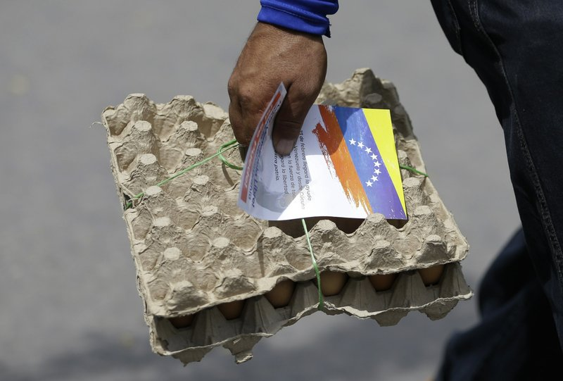 A Venezuelan man carrying a pack of eggs also clutches a flyer, given to him by Venezuelan politicians in exile, inviting people to come out to the streets on Feb. (AP Photo/Fernando Vergara)