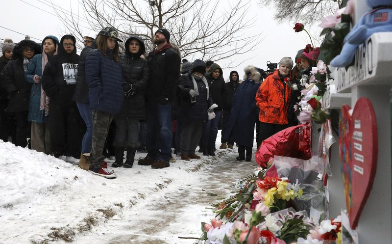 People attend at a makeshift memorial Sunday, Feb. 17, 2019, in Aurora, Ill., near Henry Pratt Co. manufacturing company where several were killed on Friday. (AP Photo/Nam Y. Huh)
