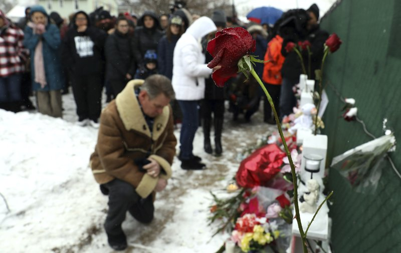 People pray at a makeshift memorial Sunday, Feb. 17, 2019, in Aurora, Ill., near Henry Pratt Co. manufacturing company where several were killed on Friday. (AP Photo/Nam Y. Huh)