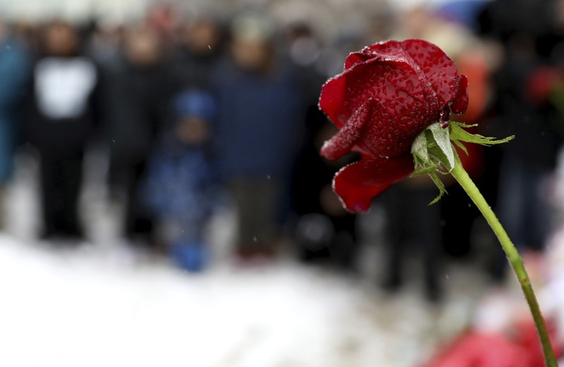 A wet rose places at a makeshift memorial Sunday, Feb. 17, 2019, in Aurora, Ill., near Henry Pratt Co. (AP Photo/Nam Y. Huh)