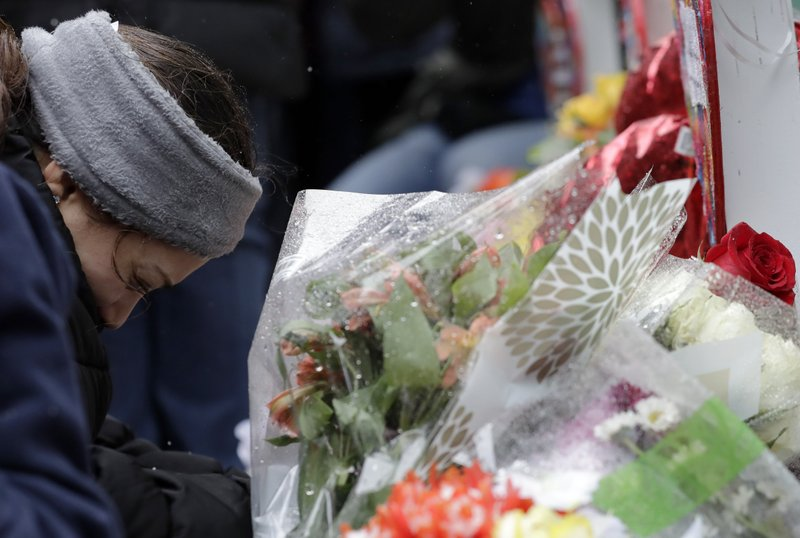 One of victim Vicente Juarez's daughter Diana Juarez cries at a makeshift memorial Sunday, Feb. 17, 2019, in Aurora, Ill. (AP Photo/Nam Y. Huh)