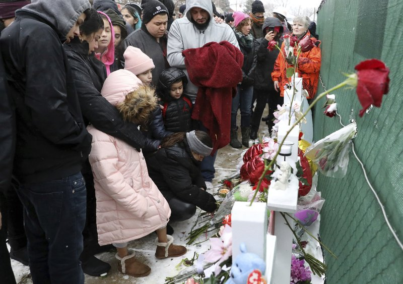 One of victim Vicente Juarez's family pray at a makeshift memorial Sunday, Feb. 17, 2019, in Aurora, Ill. (AP Photo/Nam Y. Huh)