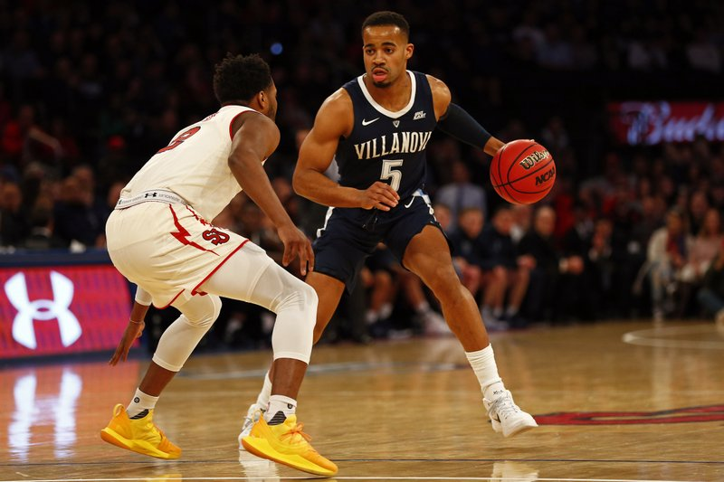 Villanova guard Phil Booth (5) looks to pass around St. John's guard Shamorie Ponds during the first half of an NCAA college basketball game Sunday, Feb. (AP Photo/Adam Hunger)