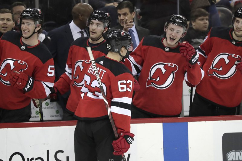 New Jersey Devils left wing Jesper Bratt (63), of Sweden, skates by the bench after scoring a goal against the Buffalo Sabres during the second period of an NHL hockey game, Sunday, Feb. (AP Photo/Julio Cortez)