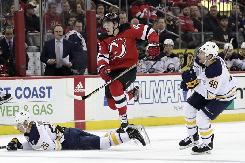 New Jersey Devils right wing Joey Anderson hops over Buffalo Sabres defenseman Rasmus Dahlin (26), of Sweden, while chasing the puck during the second period of an NHL hockey game, Sunday, Feb. (AP Photo/Julio Cortez)