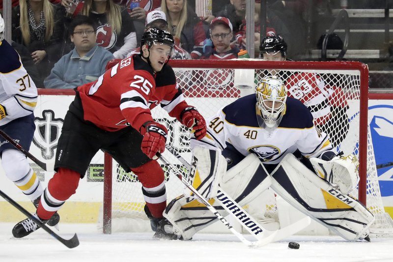 Buffalo Sabres goaltender Carter Hutton (40) protects his net as New Jersey Devils defenseman Mirco Mueller (25), of Switzerland, during the first period of an NHL hockey game, Sunday, Feb. (AP Photo/Julio Cortez)