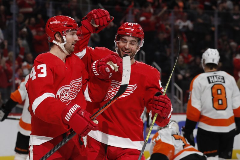 Detroit Red Wings left wing Darren Helm (43) is congratulated on his goal by teammate center Frans Nielsen (51) during the second period of an NHL hockey game against the Philadelphia Flyers, Sunday, Feb. (AP Photo/Carlos Osorio)