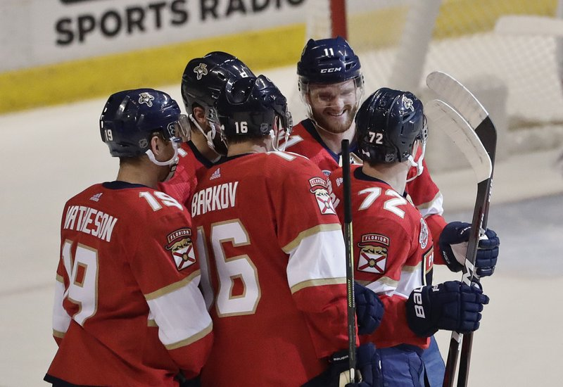 Florida Panthers left wing Jonathan Huberdeau, center, smiles at Florida Panthers center Frank Vatrano, right, along with his teammates after Vatrano score during the first period of an NHL hockey game against the Montreal Canadiens on Sunday, Feb. (AP Photo/Brynn Anderson)