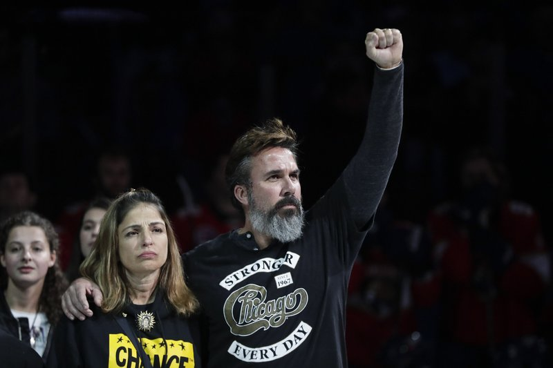 Patricia and Manuel Oliver, parents of Joaquin Oliver, who was one of the 17 people killed by a gunman at Marjory Stoneman Douglas High School, stand on the ice to honor survivors before an NHL hockey game where the Florida Panthers play the Montreal Canadiens on Sunday, Feb. (AP Photo/Brynn Anderson)