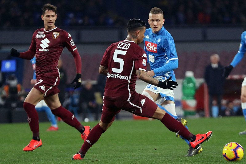 Torino's Armando Izzo, foreground, challenges Napoli's Piotr Zielinski during the Serie A soccer match between Napoli and Torino at the San Paolo stadium in Naples, Italy, Sunday, Feb. (Cesare Abbate/ANSA via AP)