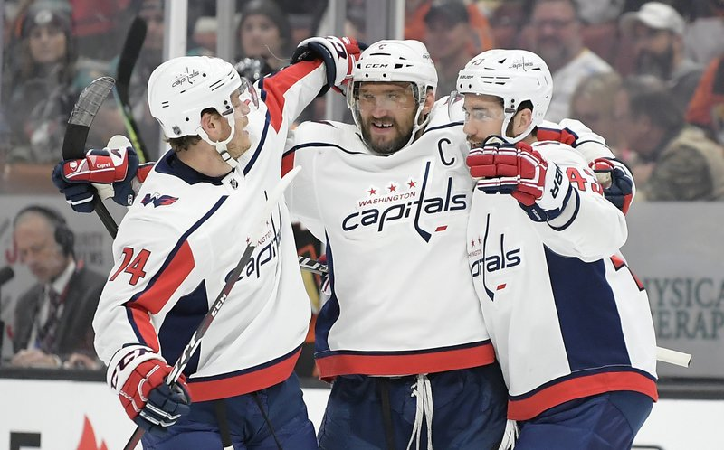 Washington Capitals left wing Alex Ovechkin, center, celebrates his goal with defenseman John Carlson, left, and right wing Tom Wilson during the first period of an NHL hockey game against the Anaheim Ducks Sunday, Feb. (AP Photo/Mark J. Terrill)