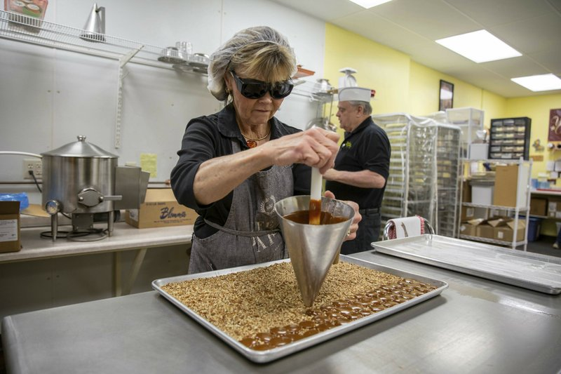 Watertown Confectionery's Vickie Marotz funnels globs of freshly-made caramel onto a tray of crushed pecans while making a batch of turtles on Wednesday, Jan. (Grace Ramey/The Public Opinion via AP)