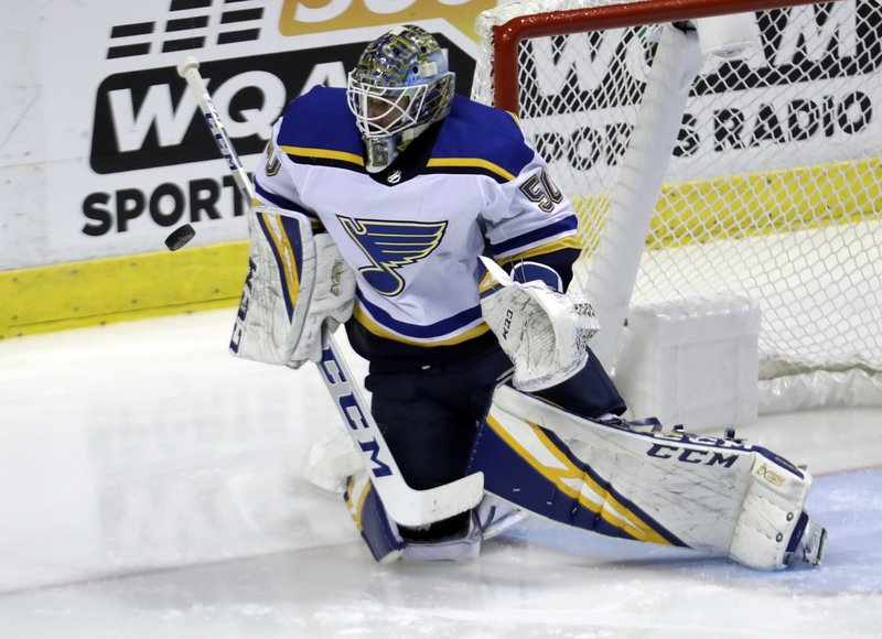 St. Louis Blues goaltender Jordan Binnington (50) deflects the puck during the third period of an NHL hockey game against the Florida Panthers, Tuesday, Feb. (AP Photo/Lynne Sladky)