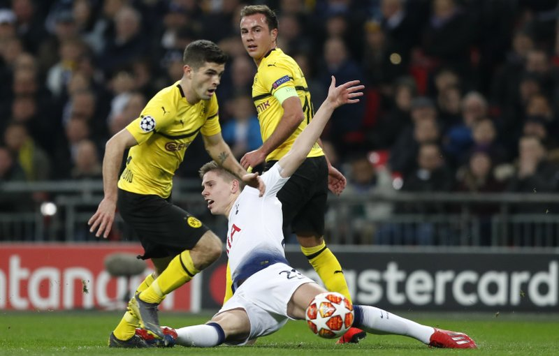 Tottenham defender Juan Foyth loses the ball to Dortmund midfielder Christian Pulisic, left, during the Champions League round of 16, first leg, soccer match between Tottenham Hotspur and Borussia Dortmund at Wembley stadium in London, Wednesday, Feb. (AP Photo/Alastair Grant)