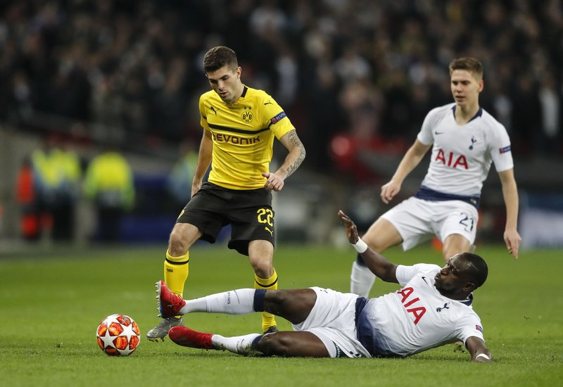 Tottenham midfielder Moussa Sissoko, down, and Dortmund midfielder Christian Pulisic, left, challenge for the ball during the Champions League round of 16, first leg, soccer match between Tottenham Hotspur and Borussia Dortmund at Wembley stadium in London, England, Wednesday, Feb. (AP Photo/Frank Augstein)