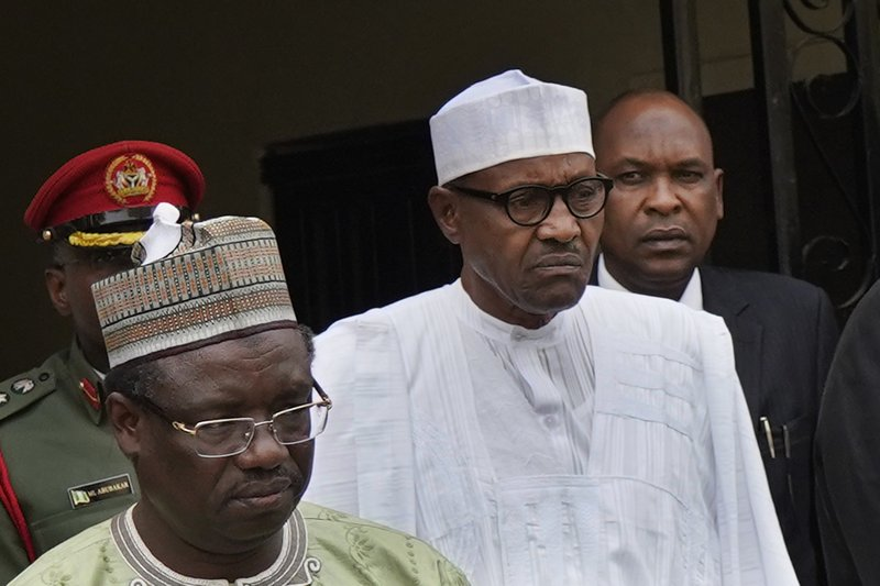 Incumbent President Muhammadu Buhari, center, leaves his party's headquarters after holding an emergency meeting with senior members of the All Progressives Congress (APC) in Abuja, Nigeria, Monday Feb. (AP Photo/Jerome Delay)
