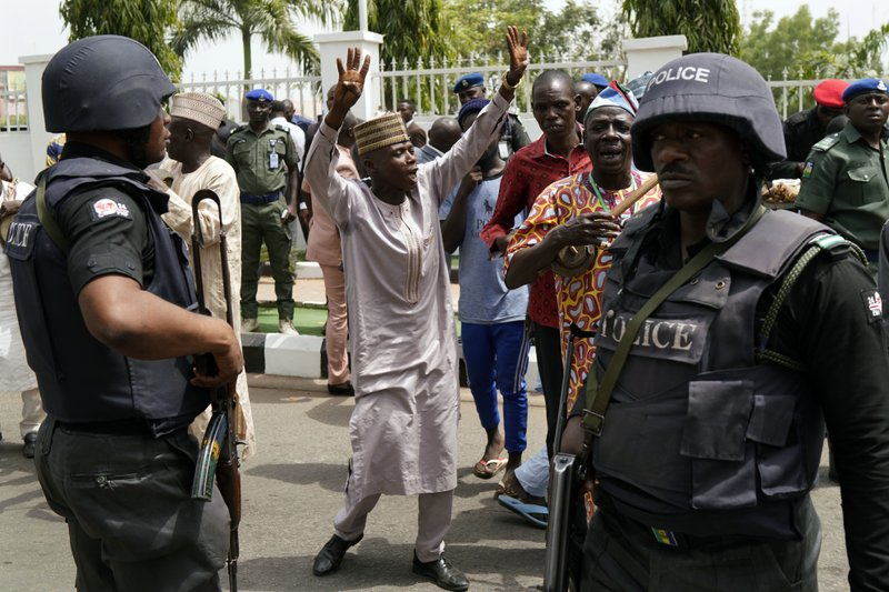 Supporters of the All Progressives Congress (APC) dance outside the party headquarters where Incumbent President Muhammadu Buhari holds an emergency meeting with senior members of the party in Abuja, Nigeria, Monday Feb. (AP Photo/Jerome Delay)