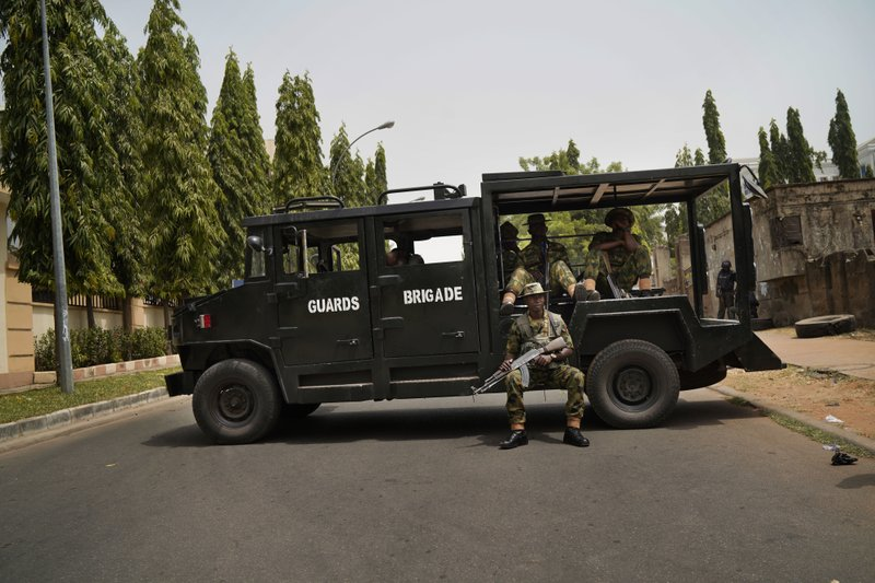 Nigerian soldiers block the road leading to the entrance of the All Progressives Congress (APC) party headquarters where Incumbent President Muhammadu Buhari holds an emergency meeting with senior members of the party in Abuja, Nigeria, Monday Feb. (AP Photo/Jerome Delay)