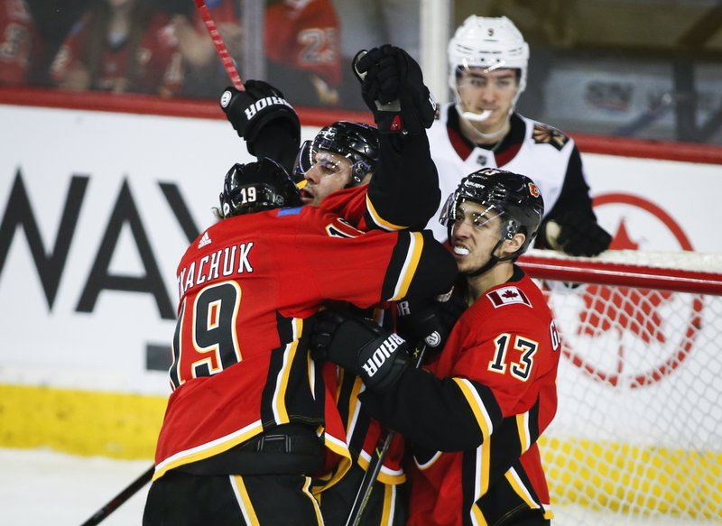 Calgary Flames' Mark Giordano, centre, celebrates his goal with teammates Matthew Tkachuk, left, and Johnny Gaudreau during second period NHL hockey action against the Arizona Coyotes in Calgary, Alberta, Monday, Feb. (Jeff McIntosh/The Canadian Press via AP)