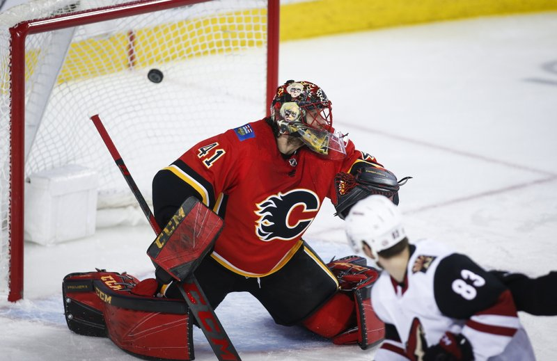 Arizona Coyotes' Conor Garland, right, scores on Calgary Flames goalie Mike Smith during second period NHL hockey action in Calgary, Alberta, Monday, Feb. (Jeff McIntosh/The Canadian Press via AP)