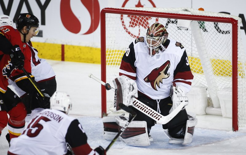 Arizona Coyotes goalie Cal Pickard, right, stops a shot from Calgary Flames' Mikael Backlund, of Sweden, during second period NHL hockey action in Calgary, Alberta, Monday, Feb. (Jeff McIntosh/The Canadian Press via AP)