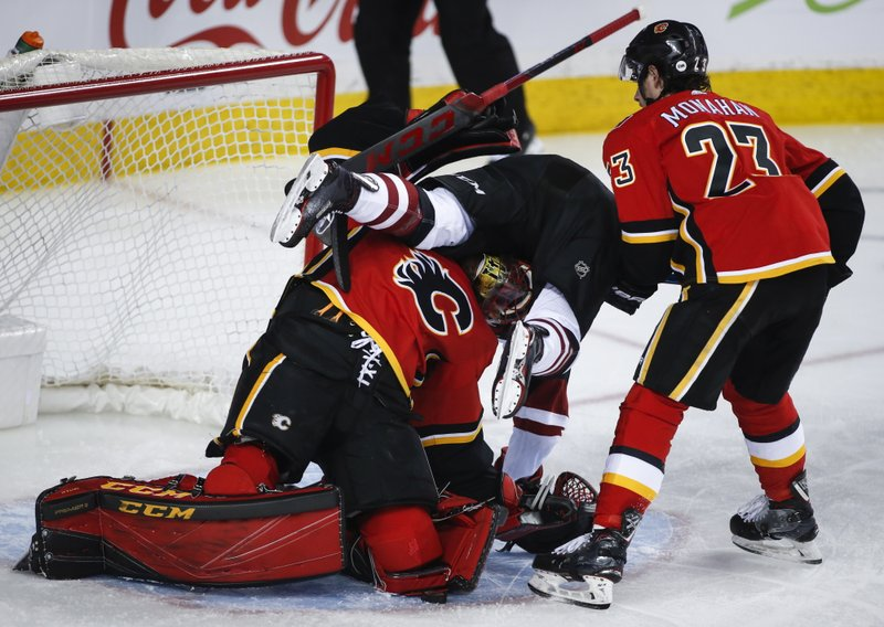 Arizona Coyotes' Nick Cousins, centre, crashes into Calgary Flames goalie Mike Smith, left, as Sean Monahan looks on during second period NHL hockey action in Calgary, Alberta, Monday, Feb. (Jeff McIntosh/The Canadian Press via AP)