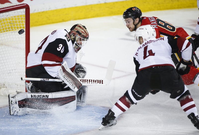 Arizona Coyotes goalie Cal Pickard deflects a shot from Calgary Flames' Andrew Mangiapane, right, during first period NHL hockey action in  Calgary, Alberta, Monday, Feb. (Jeff McIntosh/The Canadian Press via AP)