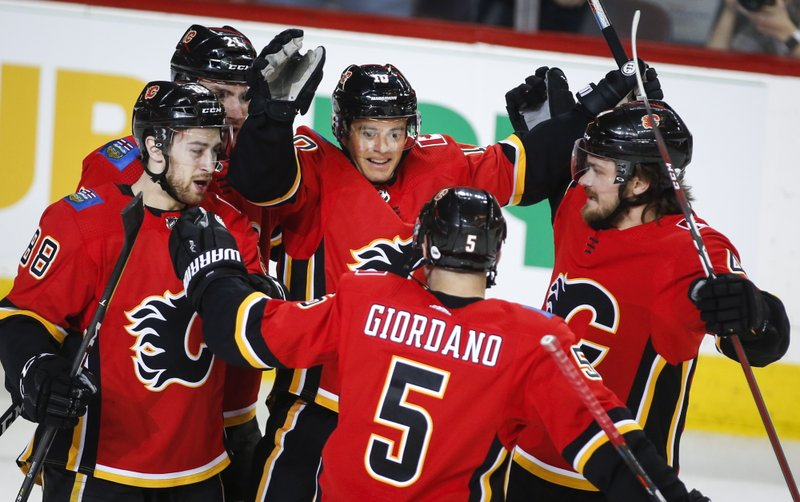 Calgary Flames' Derek Ryan (10) celebrates his goal with teammates during first period NHL hockey action against the Arizona Coyotes in  Calgary, Alberta, Monday, Feb. (Jeff McIntosh/The Canadian Press via AP)
